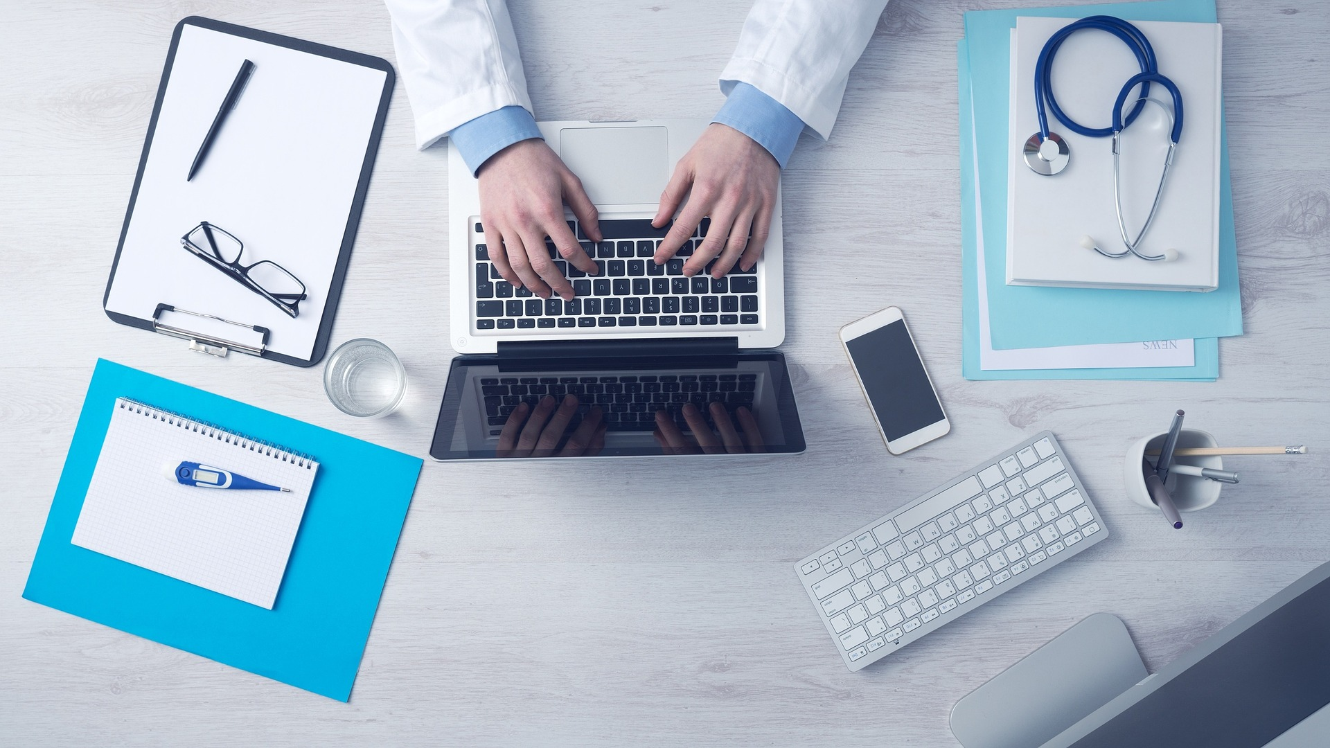 Hands typing on a laptop surrounded by medical equipment
