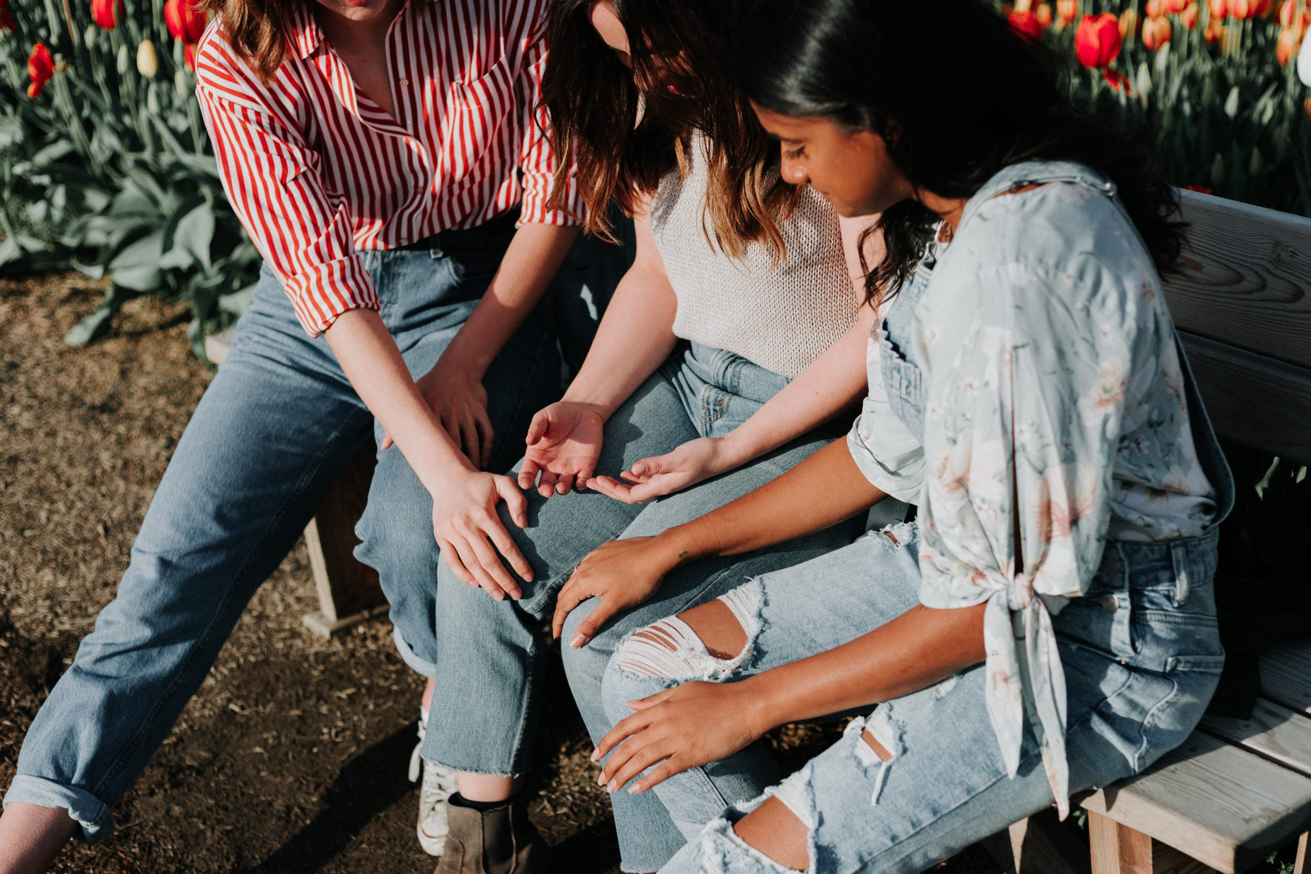 three women sitting on a bench holding hands